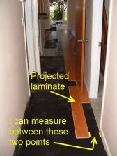 Installing laminate in hallway, taking measurement.