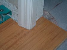 Finished door jamb with laminate flooring