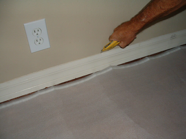 Here I am cutting the top of the baseboard where the caulking is so I ...