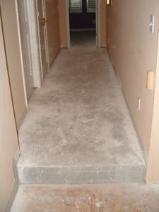 The concrete floor in the hallway after removing the carpet and padding.