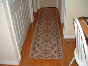 Vanier laminate flooring installed in hallway with throw rug photo