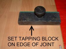 Pergo Presto from Home Depot, Here I am using a tapping block to fix the proud edge of the end joint.