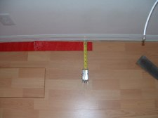 Installing the last row of laminate flooring, first measure one end.