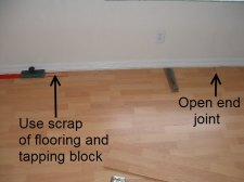 Installing the last row of laminate flooring, Here I will use a tapping block and a scrap piece of laminate to connect the end joint together.