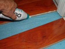 This photo is True floor laminate flooring from Ifloor.com, Color: Tiramisu Surprise, applying glue after shaving off locking system.