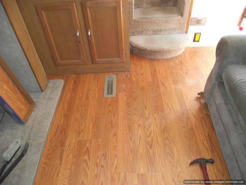Installing laminate flooring in a travel trailer, slide laminate under the step