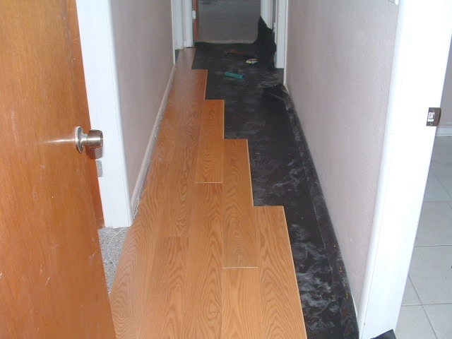 Installing laminate in hallway on the first side.