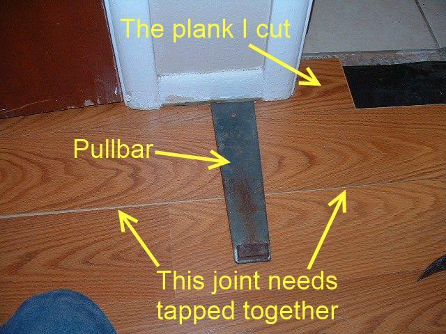 Hallways, installing the last row of laminate flooring in hallway under door jamb with pull bar.
