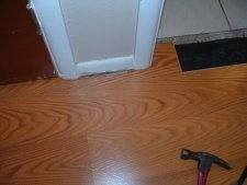 Hallways, the final result is getting this last laminate plank installed under the door jamb in the hallway.