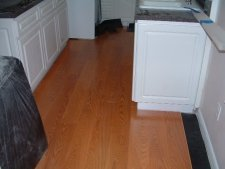 Quick step Eligna laminate flooring single board design being installed in the kitchen