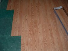 Installing Pergo Accolade laminate flooring over moisture barrier.