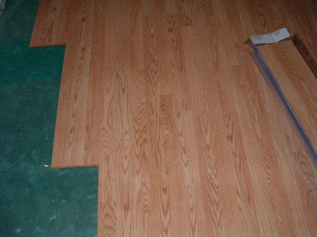 Installing Pergo Accolade laminate flooring over moisture barrier.