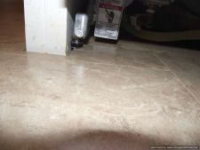 Laminate tile flooring is installed under the front legs of the disherwasher.