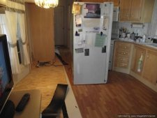 Moving the refrigerator onto the installed laminate flooring in the kitchen.