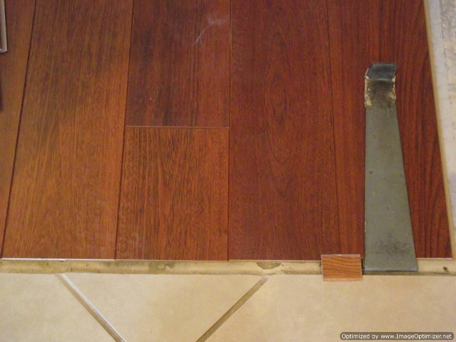 Harmics Brazilian Cherry laminate flooring with beveled edges installed up to ceramic tile, made by Unilin