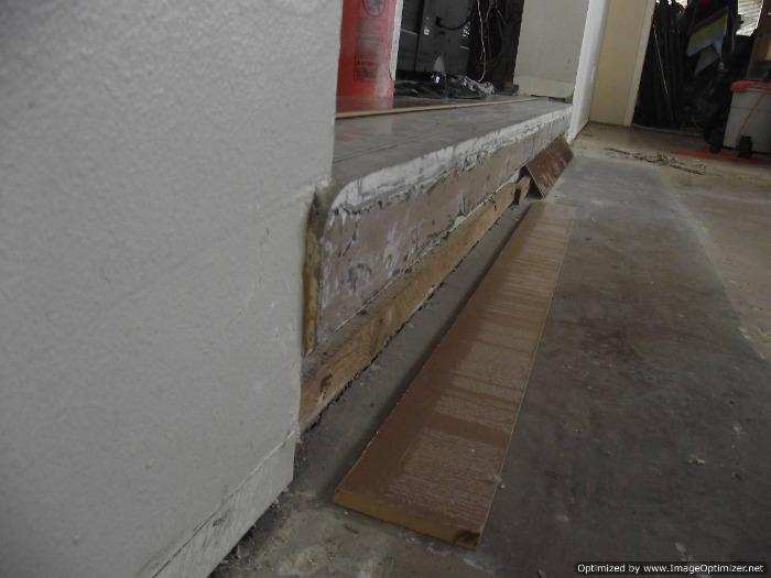Sunken living room concrete step down to have laminate flooring installed on the concrete sunken living room.