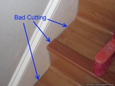 Bad laminate stair installation. It shows gaps where the treads and risers were cut, and how the stair nose was cut short and filled in with a small piece.