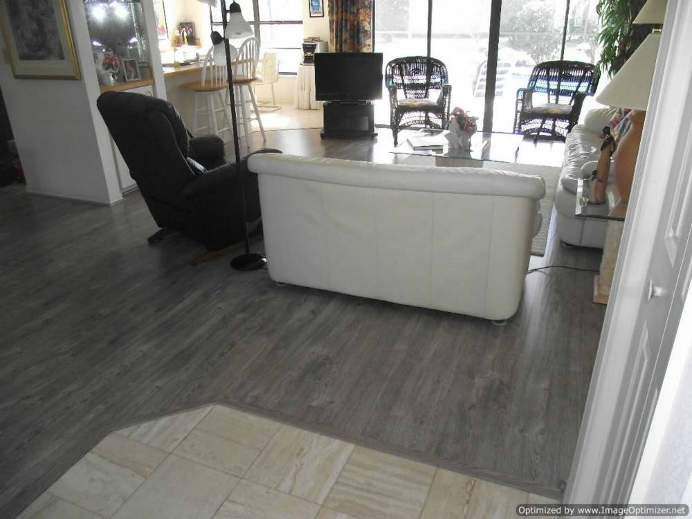 Shaw Gray laminate flooring, installed in living room and around tile entry.