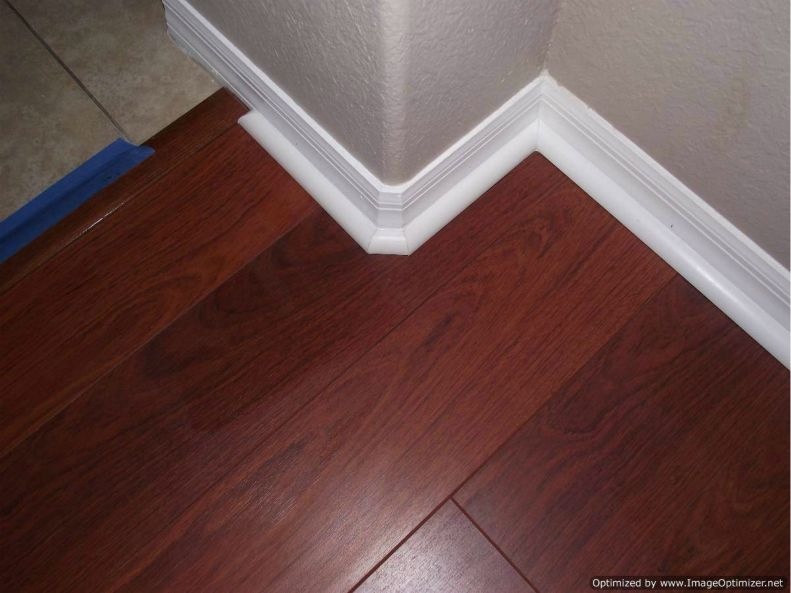 Quick Step Perspective laminate installed close up with quarter round