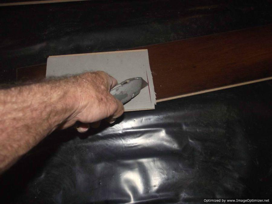 Lamton Virginia walnut laminate flooring, excess padding Being cut on back