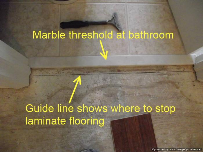 Installing laminate up to a marble threshold at a bathroom doorway, draw a guide line to show where to stop laminate flooring.