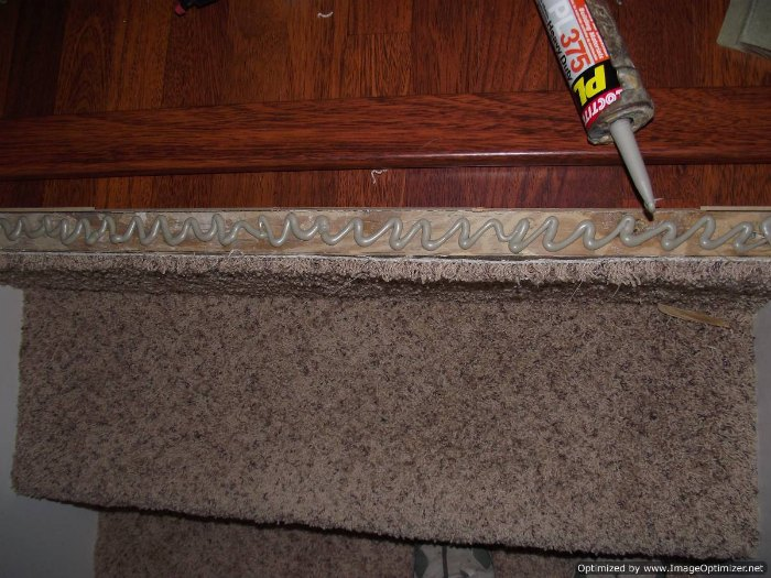 carpet laminate stairs. applying construction adhesive to the stair nose on top stair. carpet laminate stairs