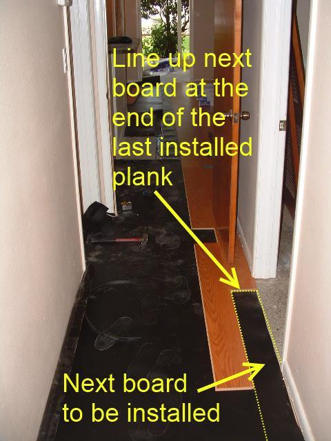Installing laminate in hallway, taking measurement.