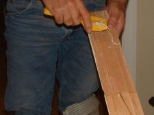 Remove the old chalking with a rasp from the back of the base board before reinstalling it.