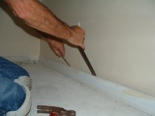 Use the pry bars to pry the baseboard away from the wall so you will not push in the drywall