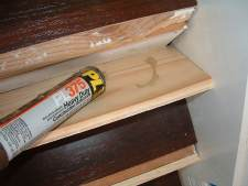 Installing risers for laminate flooring on stairs,applying glue to back of stair riser.