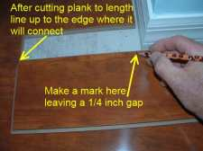 Cutting laminate around corners is easier when I install this temporary plank.
