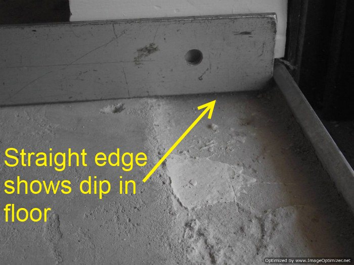 Sliding glass doors need preparation for laminate flooring installation, the straight edge shows the dip in the floor.